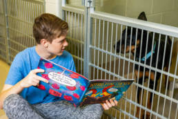 Teenage boy reading out loud to a black dog that is inside a kennel.