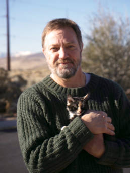 Photo of board member John Boone holding a kitten.