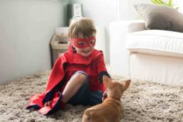 Photo of child in superhero costume playing with dog.