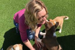 Executive Director Jill holding a basketball and touching noses with a puppy.