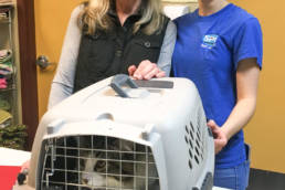 Photo of Cathy and Alyssa standing next to a cat inside a crate, smiling.