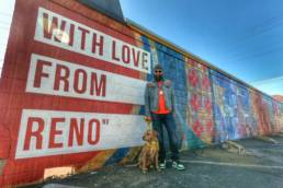 Man standing with dog in front of a graffiti wall.