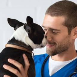 Veterinary technician smiling at dog.