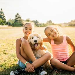 two smiling girls with a goldendoodle in their lap