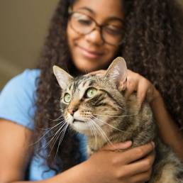 Young woman with glasses gently holding a cat.
