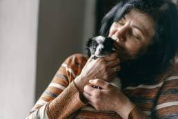 Woman holding a small black and white puppy.