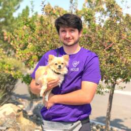 Eddie holding golden pomeranian in his arms.