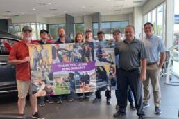 Subaru team and Sean Farnan holding Subaru adoption collage.